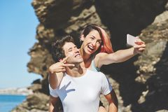Happy woman taking selfie riding on her boyfriend back. Portrait of happy women taking selfie riding on her boyfriend back Stock Image