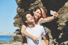 Happy woman taking selfie sitting on her boyfriend back. Portrait of happy women taking selfie sitting on her boyfriend back Stock Image