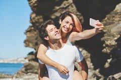 Happy woman taking selfie sitting on her boyfriend back Stock Image