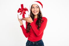 Portrait of a happy wondering asian woman. Dressed in red santa hat holding gift box and looking away at copy space isolated over white background Royalty Free Stock Images