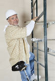 Portrait of a happy worker climbing scaffold Stock Photos