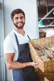 Portrait of happy worker holding basket of bread Royalty Free Stock Images