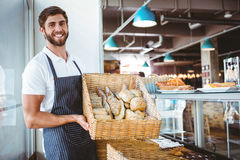 Portrait of happy worker holding basket of bread Stock Photography