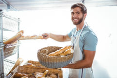Portrait of happy worker holding basket of bread Stock Photo