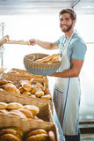 Portrait of happy worker holding basket of bread Stock Images