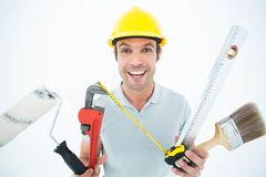 Portrait of happy worker holding various equipment Stock Image