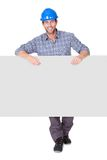Portrait of happy worker presenting empty banner Stock Photo