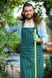 Portrait of happy worker standing with tool at garden. Portrait of happy young male worker standing with tool at community garden Stock Photography