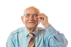 Portrait of happy 90 year old senior man holding glasses, smiling and looking at camera isolated on white background stock image