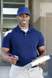 Portrait of a happy young African American delivery man with clipboard Royalty Free Stock Photography