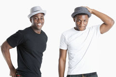 Portrait of happy young African American men wearing hats over gray background royalty free stock images
