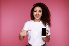 Portrait of a happy young african girl showing plastic credit card while holding mobile phone isolated over yellow royalty free stock images