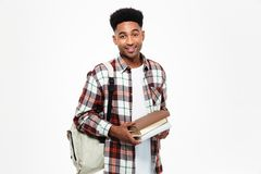 Portrait of a happy young african male student. Dressed in plaid shirt with a backpack holding books and looking at camera isolated over white background Royalty Free Stock Photos