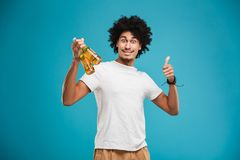 Portrait of a happy young african man. Holding beer bottles and showing thumbs up isolated over blue background Royalty Free Stock Image