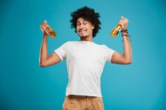 Portrait of a happy young african man. Showing beer bottles isolated over blue background Stock Photography