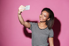 Portrait of a happy young african woman taking selfie. And posing isolated over pink background Royalty Free Stock Photos