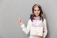 Portrait of a happy young arabian woman. Holding stack of present boxes and pointing finger away isolated over gray background Stock Photos