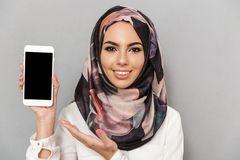 Portrait of a happy young arabian woman. Showing blank screen mobile phone isolated over gray background Royalty Free Stock Photo