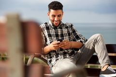 Happy young arabic man sending text message on mobile phone. Portrait of happy young arabic man sending text message on mobile phone Stock Photo
