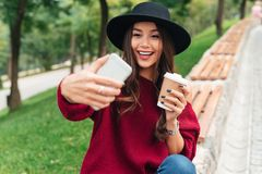 Portrait of a happy young asian girl. Dressed in hat and sweater holding coffee cup while sitting on a bench and taking a selfie outdoors Royalty Free Stock Photos