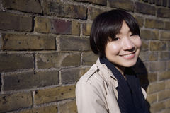 Portrait of a happy young Asian woman against wall Stock Photography