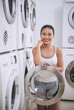 Dormitory laundry room. Portrait of happy young Asian woman opening door of washing machine in laundry room of dormitory stock photo