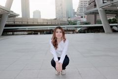 Portrait of happy young Asian woman posing in a squatting position on sidewalk at urban city background. royalty free stock images