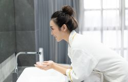 Portrait of happy young Asian woman while washing her face and  looking to mirror at bathroom.Natural skin care and people Concept.  royalty free stock image