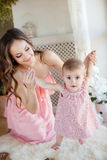Portrait of happy young attractive mother playing with her baby girl near window in interior at haome. Pink dresses on mother and Stock Photography