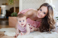 Portrait of happy young attractive mother playing with her baby girl near window in interior at haome. Pink dresses on mother and Royalty Free Stock Photo