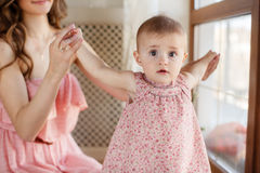 Portrait of happy young attractive mother playing with her baby girl near window in interior at haome. Pink dresses on mother and Stock Photo