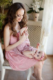 Portrait of happy young attractive mother playing with her baby girl near window in interior at haome. Pink dresses on mother and Royalty Free Stock Photography