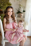 Portrait of happy young attractive mother playing with her baby girl near window in interior at haome. Pink dresses on mother and Royalty Free Stock Images
