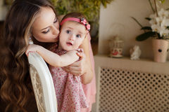 Portrait of happy young attractive mother playing with her baby girl near window in interior at haome. Pink dresses on mother and Royalty Free Stock Image