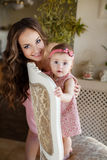 Portrait of happy young attractive mother playing with her baby girl near window in interior at haome. Pink dresses on mother and Stock Photos
