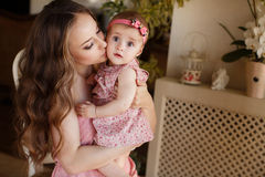 Portrait of happy young attractive mother playing with her baby girl near window in interior at haome. Pink dresses on mother and Stock Images