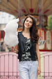 Portrait of happy young beautiful brunette woman in black leather jacket posing in amusement park with candy-floss Royalty Free Stock Photography