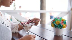 Portrait of happy young beautiful girl eating a dessert in restaurant on the seashore.