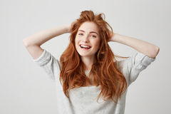 Portrait of happy young beautiful redhead girl smiling looking at camera touching hair over white background. Royalty Free Stock Images