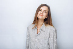 Portrait of happy young beautiful woman in big shirt posing against white studio background Stock Photos