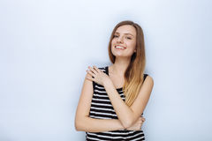 Portrait of happy young beautiful woman in striped shirt hugging herself posing for model tests against white studio background Stock Photo