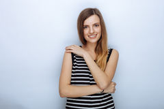 Portrait of happy young beautiful woman in striped shirt hugging herself posing for model tests against white studio background Royalty Free Stock Image