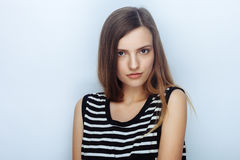 Portrait of happy young beautiful woman in striped shirt posing for model tests against studio background Stock Images