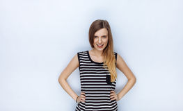 Portrait of happy young beautiful woman in striped shirt showing her tongue posing hands on hips for model tests against white stu Stock Photos