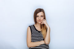 Portrait of happy young beautiful woman in striped shirt touching her cheek posing for model tests against white studio background. Portrait of happy young stock photos