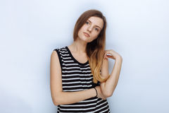 Portrait of happy young beautiful woman in striped shirt touching her hair posing for model tests against white studio background Stock Photo