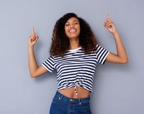 Happy young black woman smiling and pointing up Stock Image