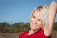 Happy young blond woman. Portrait of happy young blond woman with arm behind head, countryside background Stock Image