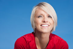 Happy young blond woman. Portrait of happy young blond woman with blue studio background Royalty Free Stock Photography