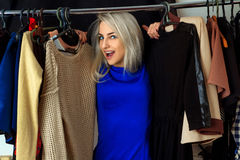 Portrait of happy young blonde woman in clothing store Stock Images